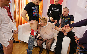 Sparkling woman enjoys cumshot of seven men on her body