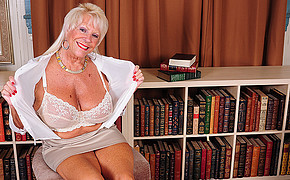 Busty MILF sitting next to the bookcase is showing her great lingerie