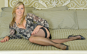 Busty blonde MILF wearing stockings and heels is touching her great leg