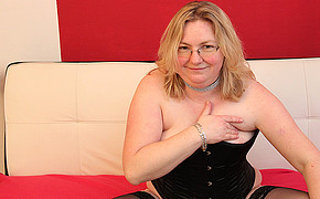 Chubby blonde with glasses is using her fingers to torture her melons